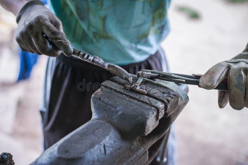 Metal de limpieza con un martillo después de soldar con autógena imágenes de archivo libres de regalías