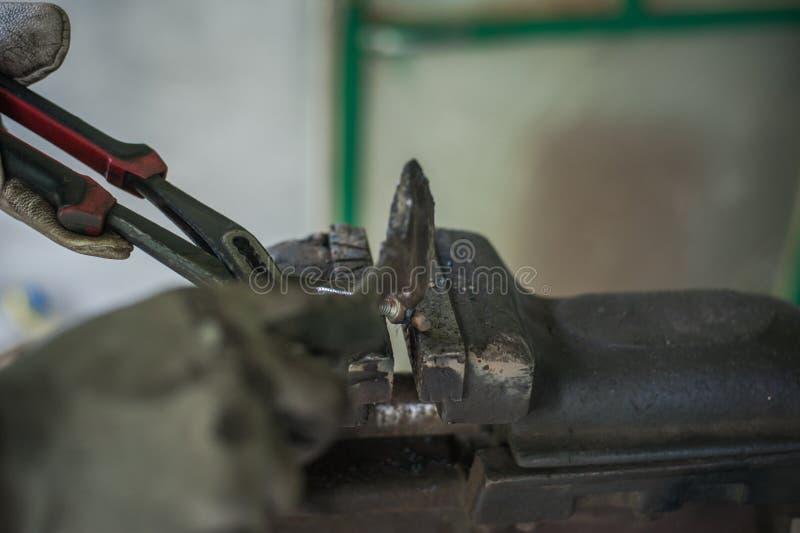 Metal de limpieza con un martillo después de soldar con autógena imagen de archivo libre de regalías