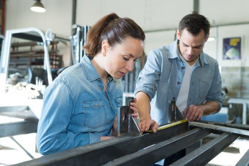 Metal de medición de la longitud del hombre y de la mujer en taller fotos de archivo