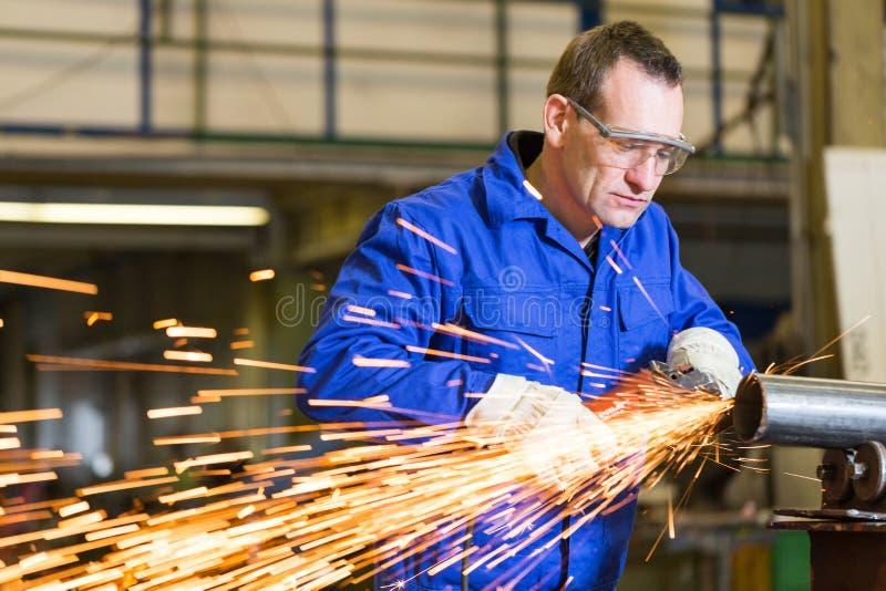 Metal de moedura do trabalhador da construção de aço com moedor de ângulo fotografia de stock royalty free