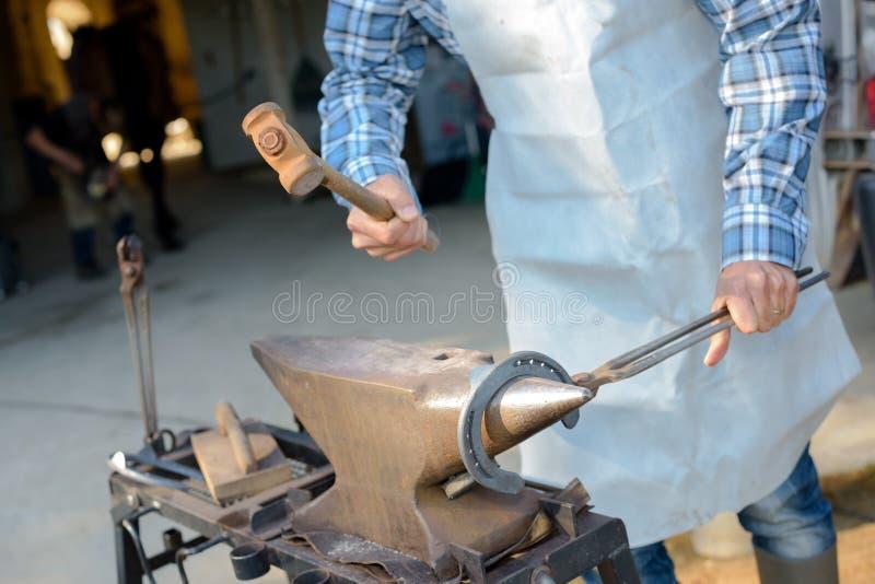 Metal de trabalho do ferreiro com martelo fotos de stock