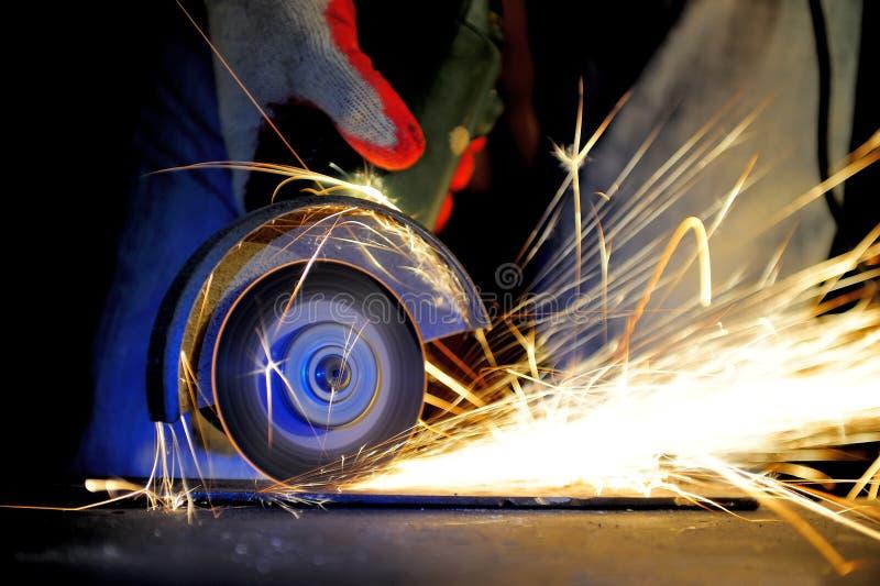 Metal del corte del trabajador con la amoladora fotografía de archivo libre de regalías