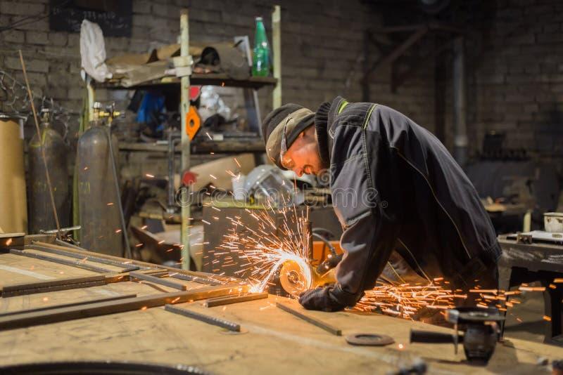 Metal del sawing del herrero con la sierra circular de la mano imagen de archivo