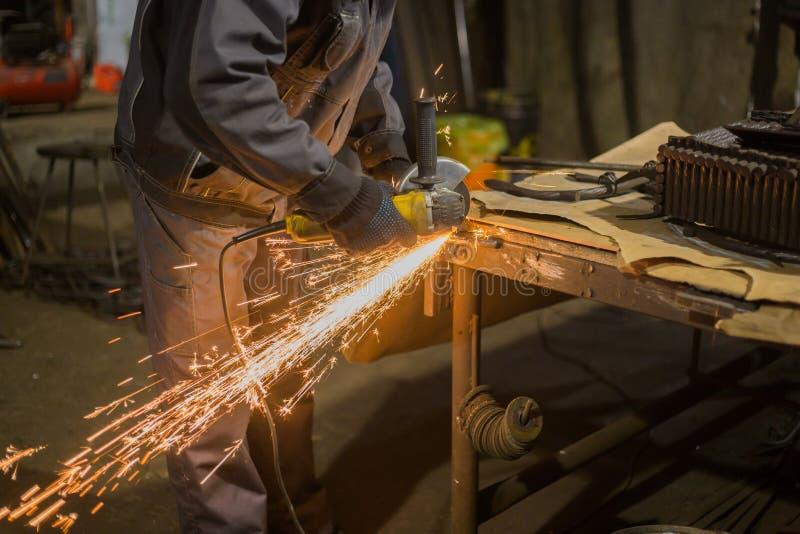 Metal del sawing del herrero con la sierra circular de la mano imágenes de archivo libres de regalías