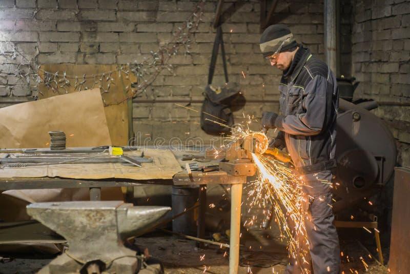 Metal del sawing del herrero con la sierra circular de la mano foto de archivo
