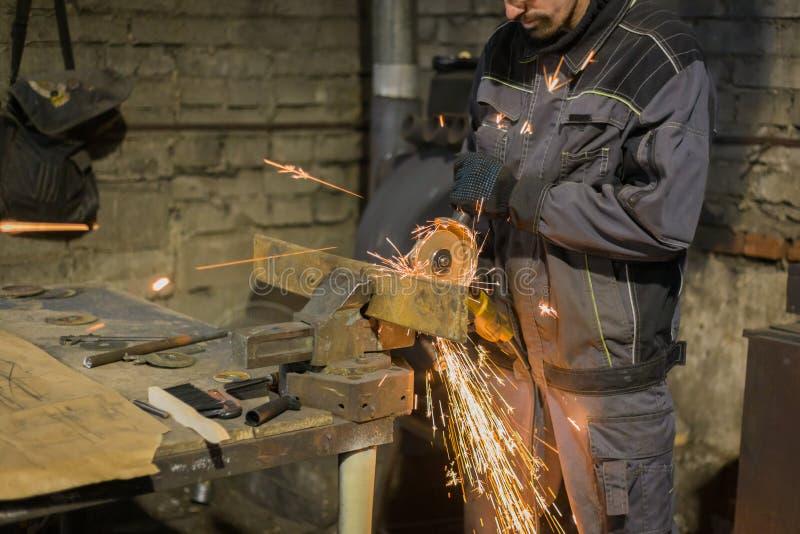 Metal del sawing del herrero con la sierra circular de la mano imagen de archivo libre de regalías
