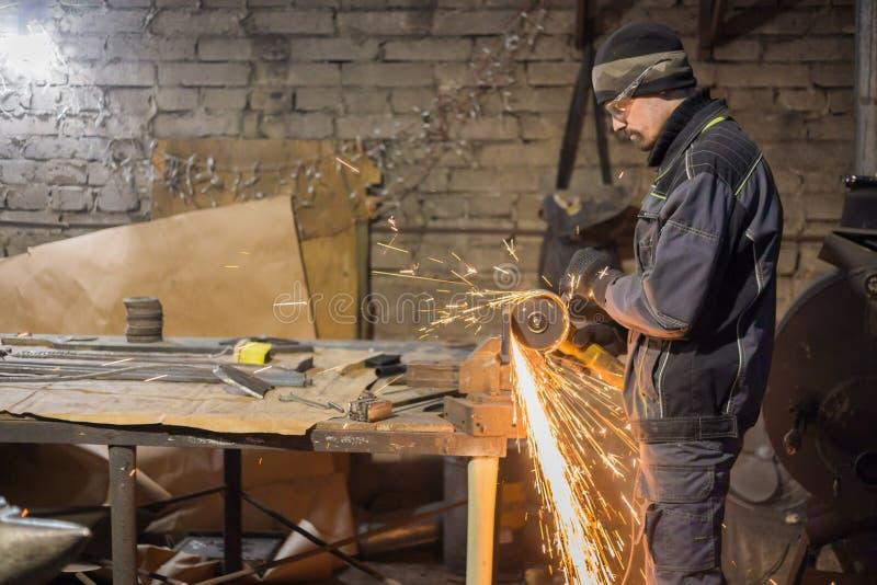Metal del sawing del herrero con la sierra circular de la mano fotografía de archivo