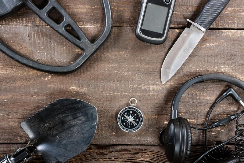 Metal detector accessories placed on old rustic wooden table. stock images