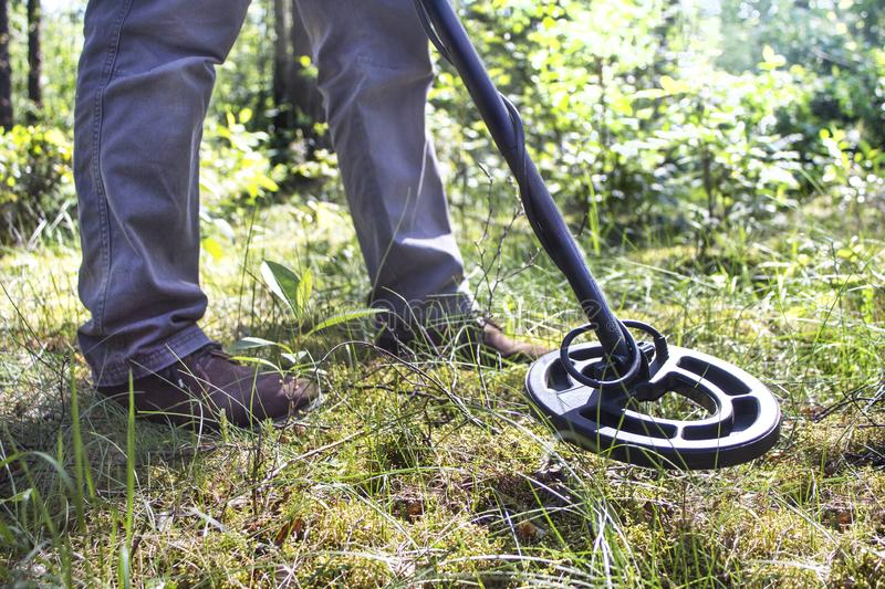 Metal detector coil and the legs of a man looking for a treasure against the background of the forest. The metal detector coil and the legs of a man looking for royalty free stock photos