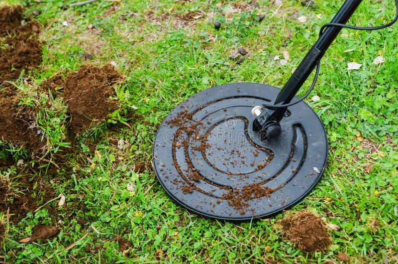 Metal detector searching for treasure in the ground stock images
