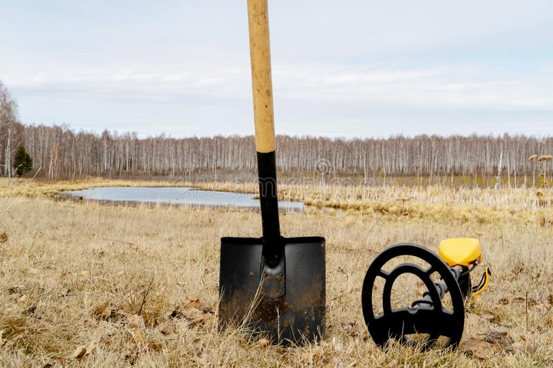 Metal detector and shovel stuck in the ground, equipment for metal searching stock photos