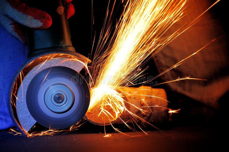 Metal do corte do trabalhador com moedor foto de stock