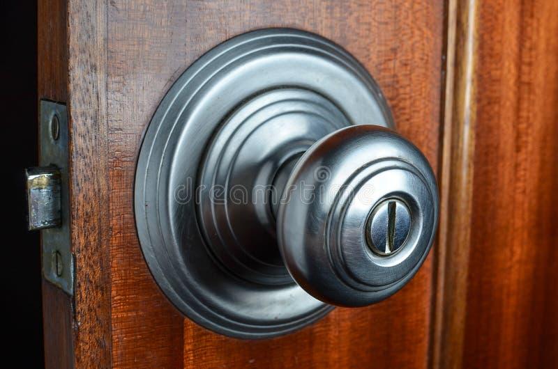 Metal door knob on open wooden door with latch stock image