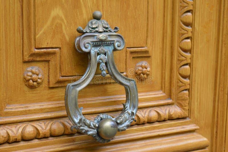 Metal door lock for knocking. Photo of metal door lock for knocking on wooden door, close up view stock photo