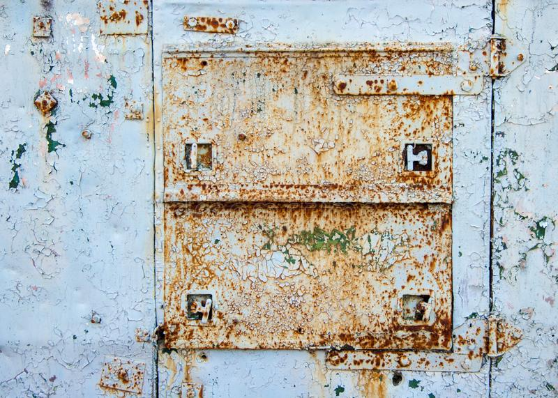 Metal door on an old iron wagon - Old age, vintage, metal corrosion, layers of old peeling paint of different colors stock photography