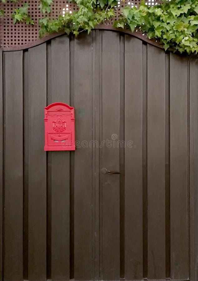 Metal door and red mailbox. Metal door, red mailbox and ivy stock image