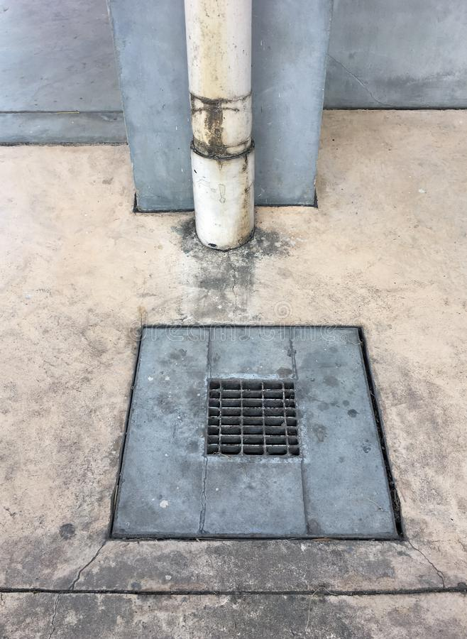 Metal drain cover on the cement floor. Near the drain pipe on the wall fo the factory stock photos
