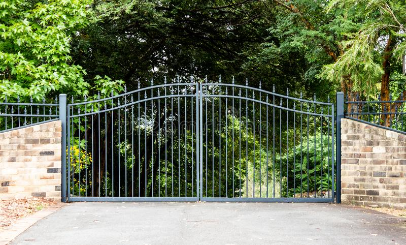 Metal driveway property entrance gates set in brick fence with garden trees  in background. Metal driveway property entrance gates in brick fence with garden royalty free stock photos