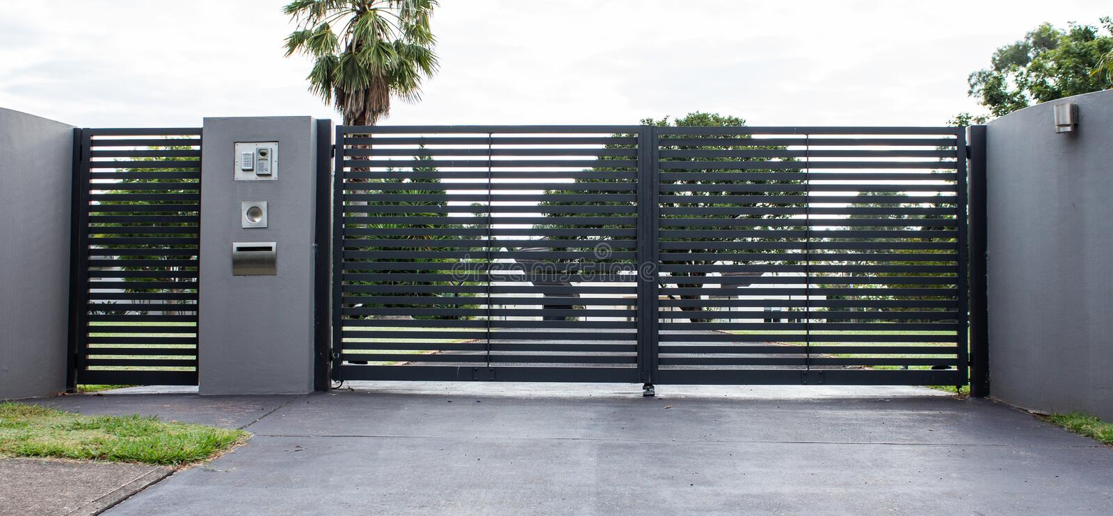 Metal driveway property entrance gates set in concrete fence with garden trees  in background. Metal driveway property entrance gates in concrete fence with royalty free stock photography