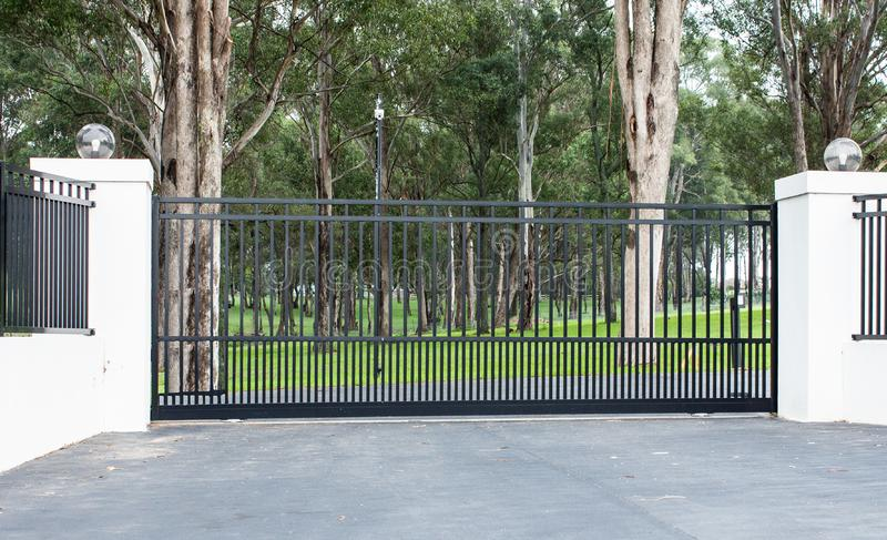 Metal driveway rural property entrance gates set in brick fence with lights and eucalyptus gum trees in background. Metal driveway entrance gates set in brick royalty free stock photos