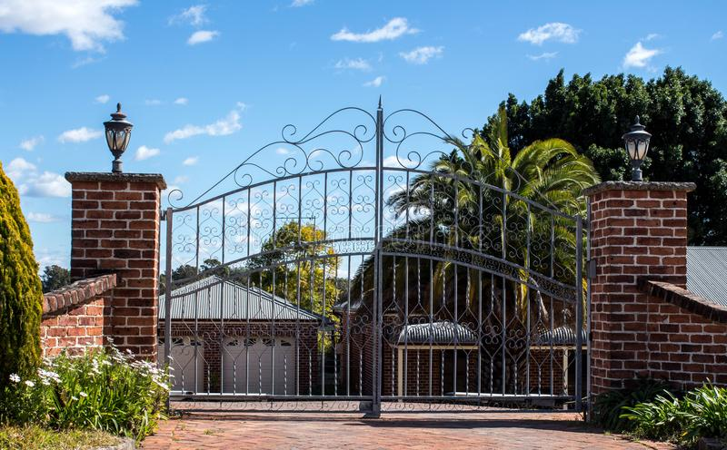 Metal driveway security entrance gates set in brick fence with residential garden in background against blue sky. Metal driveway security entrance gates set in stock images