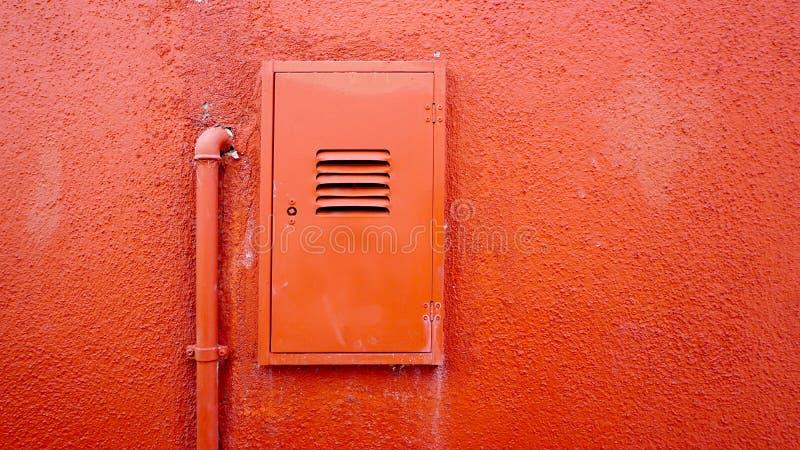 Metal drymba i elektryczny pudełko na pomarańczowej kolor ścianie zdjęcie stock