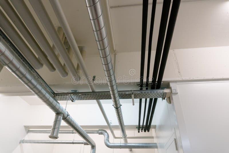 Metal e sistema de tubulação plástico no teto da adega de um prédio de apartamentos imagem de stock royalty free