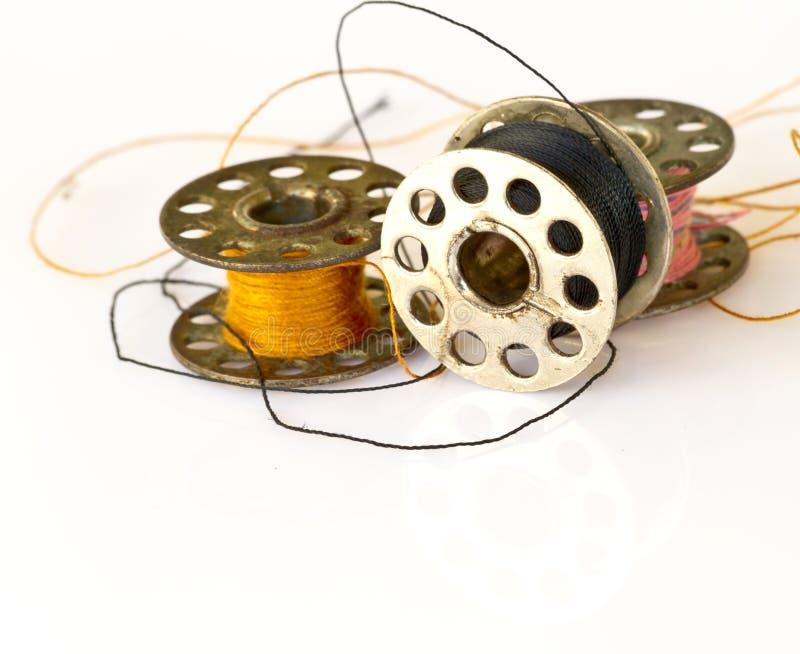 Metal el carrete de las bobinas del hilo o de la máquina de coser aisladas en pizca foto de archivo libre de regalías