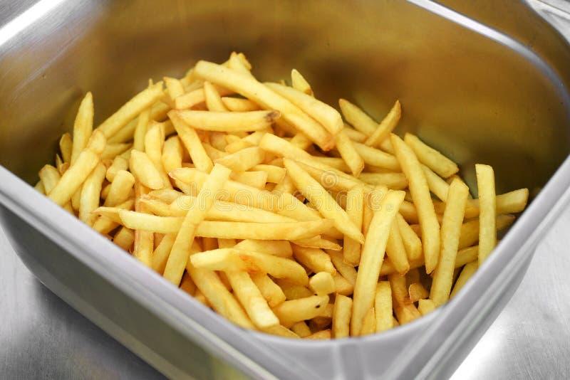 Metal el compartimiento llenado de las patatas fritas curruscantes de oro foto de archivo