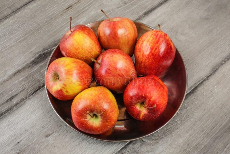 Metal el cuenco por completo de manzanas maduras rojas colocadas en el escritorio de madera gris fotografía de archivo