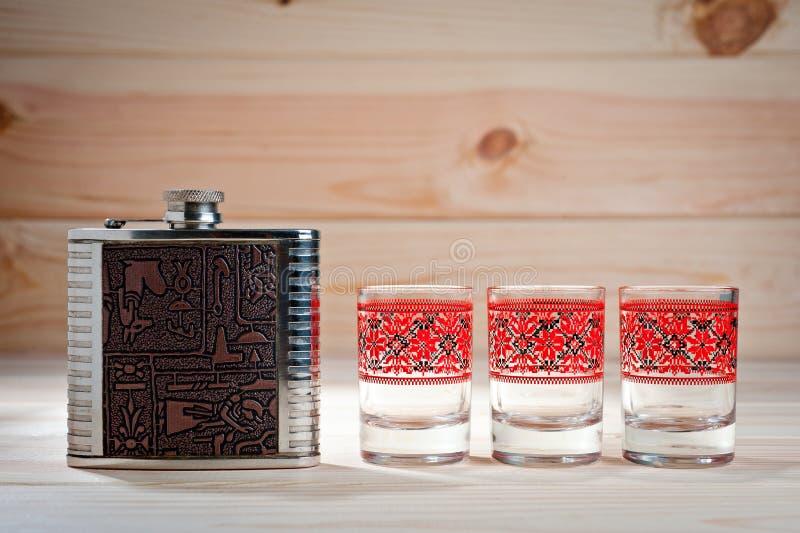 Metal el frasco para las bebidas alcohólicas y tres vidrios en un fondo de madera fotografía de archivo libre de regalías