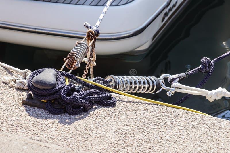 Metal el listón para amarrar los barcos, empernado a la tierra, con la primavera del amortiguador de la cuerda y de choque foto de archivo