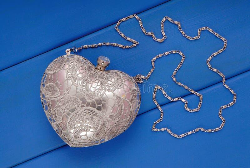 Metal evening handbag with chain, handbag is on blue stock photos