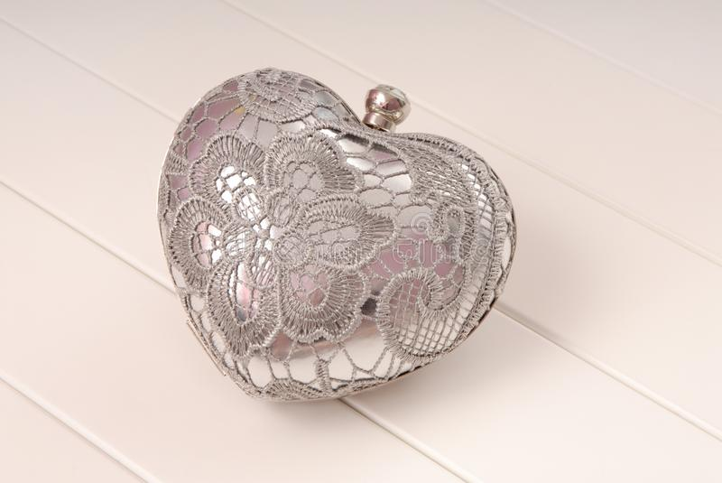 metal evening handbag, clutch has heart shape, handbag is on white background, sparkly grey handbag royalty free stock image
