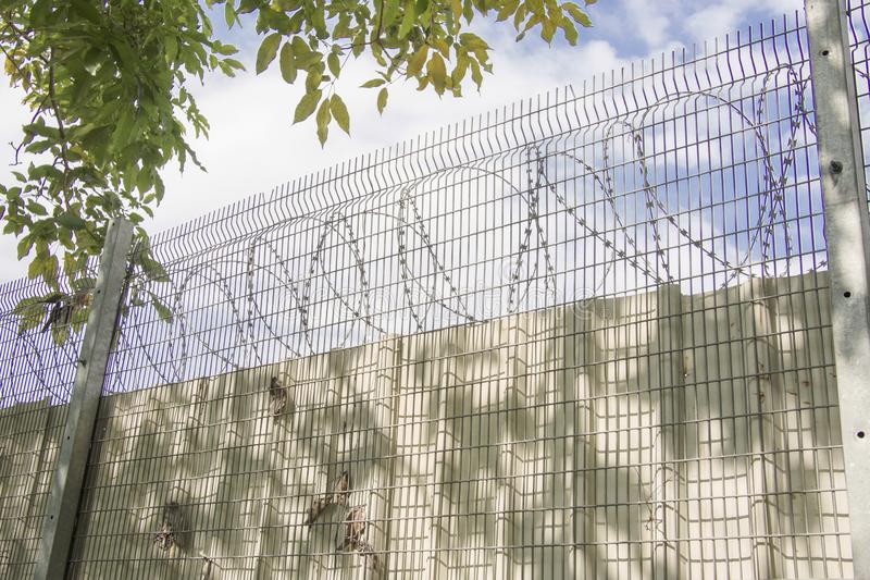 Metal fence with barbed wire against a blue sky. royalty free stock images