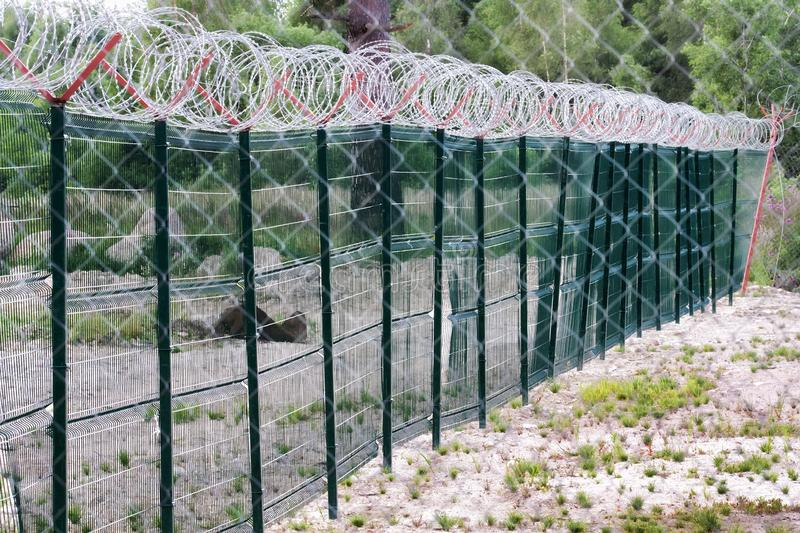 Metal fence with barbed wire stock images