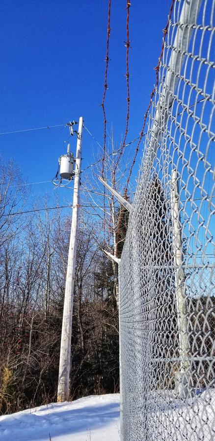 Metal fence. Barbed wire. Electric pole.  Bleu sky. Trees. Winter . Snow. stock photos