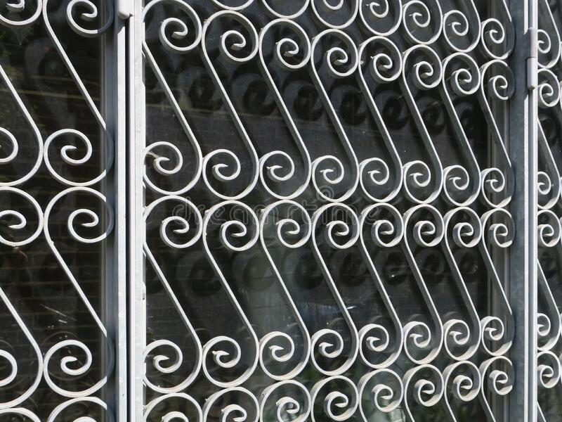 Metal fence formed by gray painted spirals in a grid stock photo