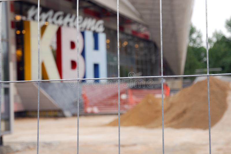 Metal fence net against blurred background of KVN club logo in Moscow royalty free stock image