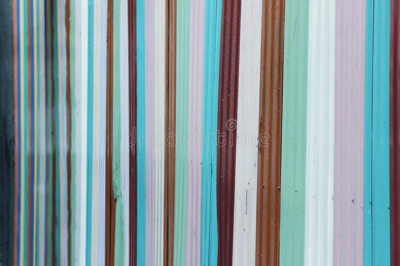metal fence, painted with stripes and paint in different colors. stock photography