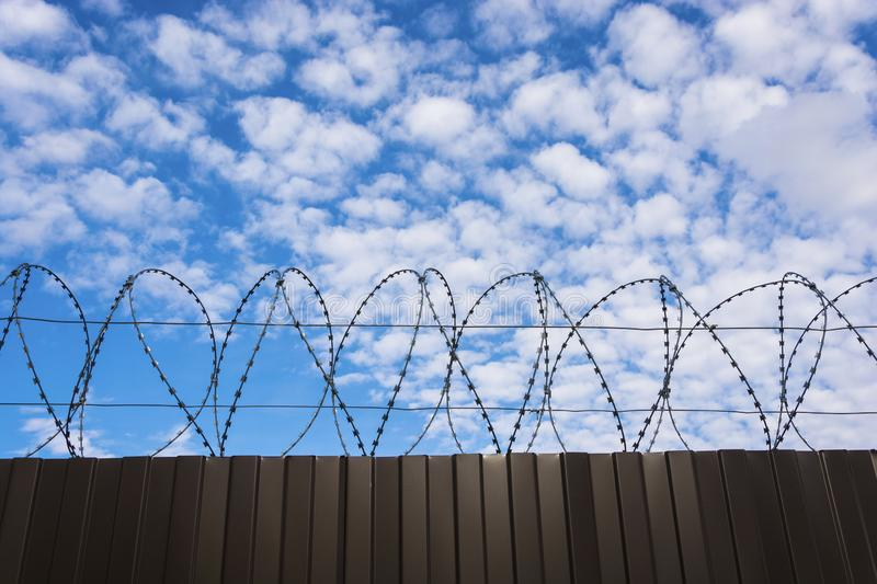 Metal fence from a sheet profile with barbed wire against a cloudy sky stock photo