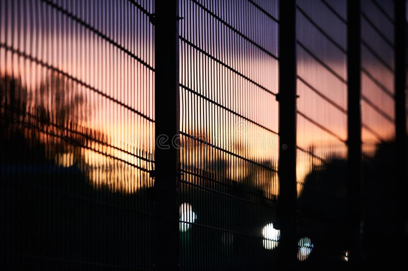 Metal fence and sky at sunset royalty free stock images