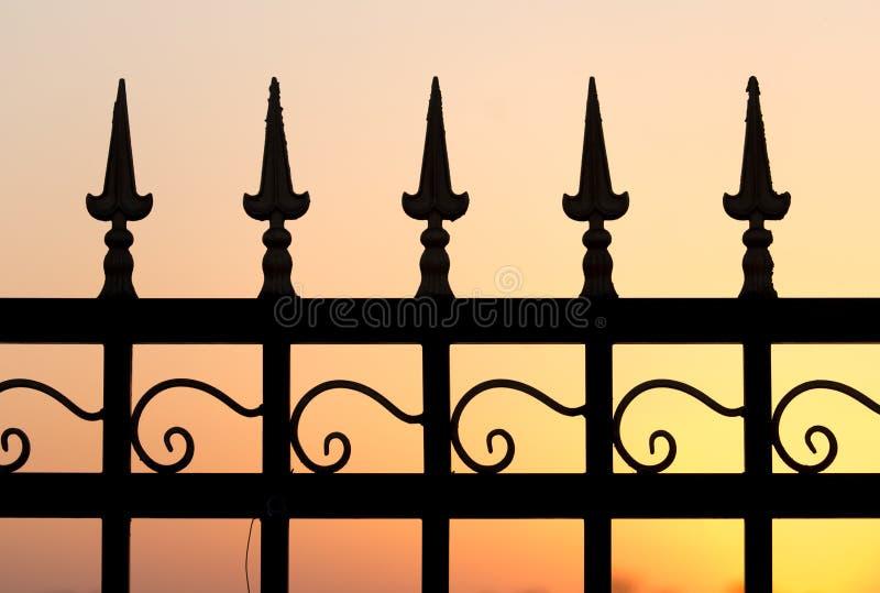 Metal fence at sunset royalty free stock photos