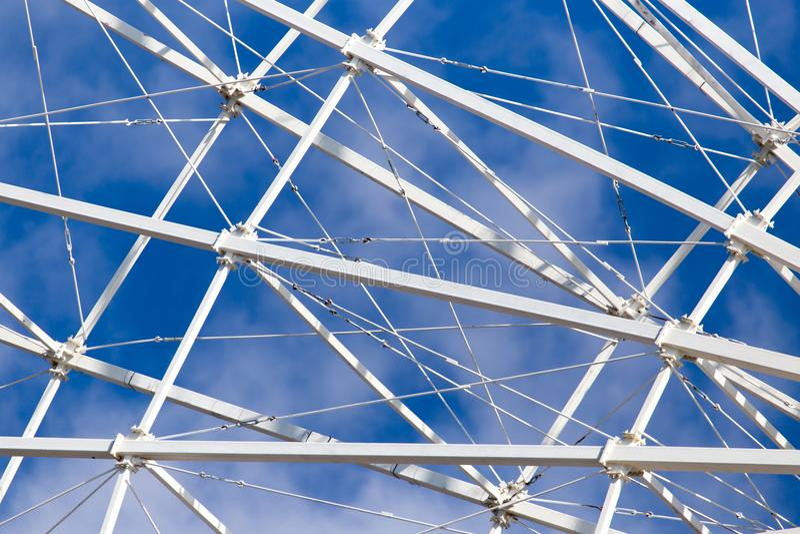 Metal Ferris wheel against the blue sky stock photo