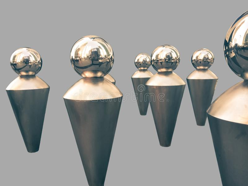 Metal figures in the form of a pawn. Modern design. Hi Tech Architecture. Figures depict a faceless crowd, art, steel, statue, hi-tech, street, iron, white royalty free stock photos