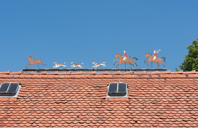 Metal figures hunt scene with hunter, deer and dogs roof of a estate royalty free stock photography