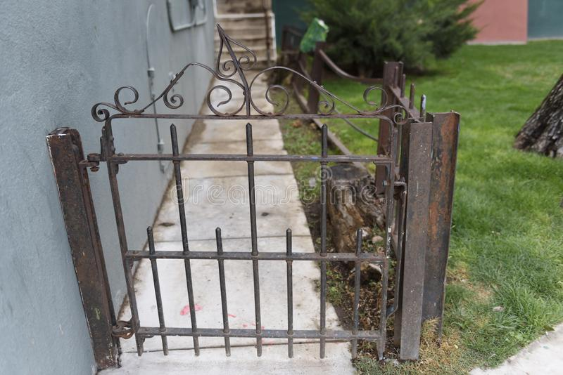 Old metal gate with metal Filigree on fence post royalty free stock image