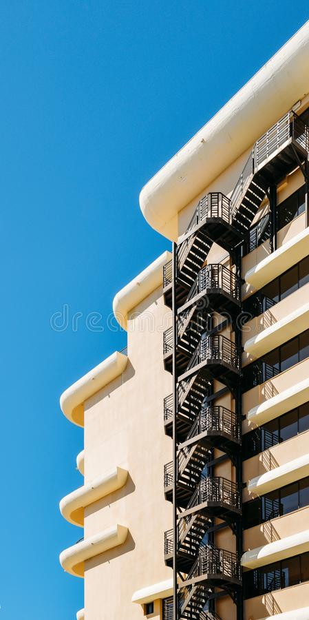 Metal fire escape on facade of modern building with blue sky.  royalty free stock photo