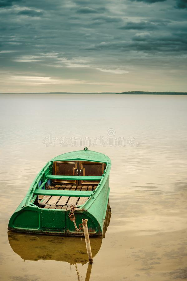 metal fishing boat moored off the lakeshore in shallow water stock images