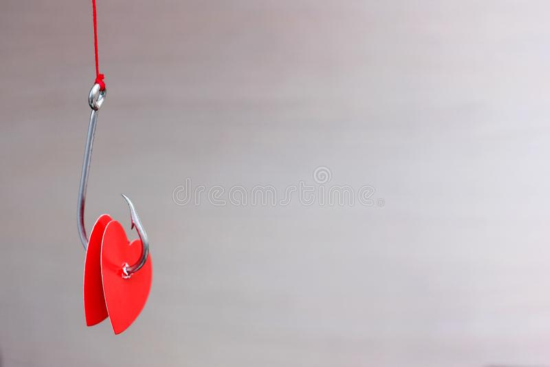 A metal fishing hook hanging on a rope pierced tow hearts of the red cardboard. Concept of love. Valentine`s day. A metal fishing hook hanging on a rope pierced stock photo
